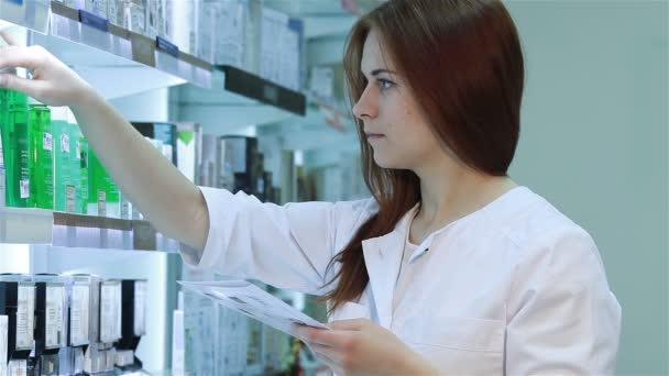 Young female pharmacist selecting a medication