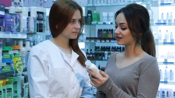 Pharmacist and female customer reading part
