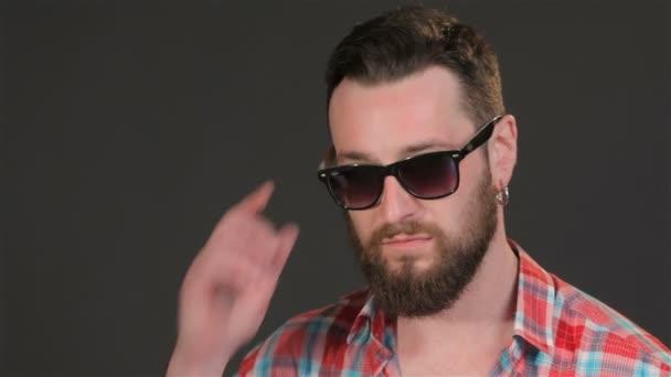 Bearded man lowers his sunglasses