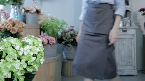 Ženské květinářství podřepu poblíž váza s květinami