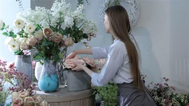Ženské květinářství stěhování květin u okna v květinářství