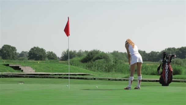 Ženu vytáhnout míč do díry v golf