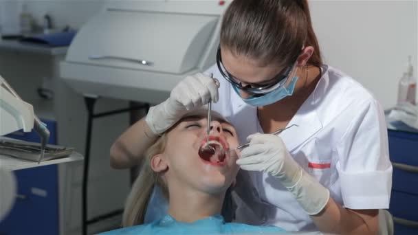 Zubní lékař aplikuje zubní sonda zkoumat pacientů zuby