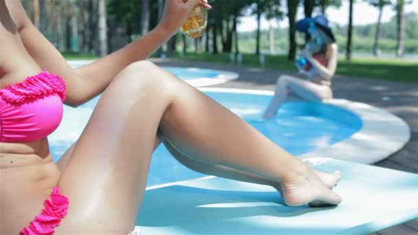 Woman uses tanning spray to her legs near the swimming pool