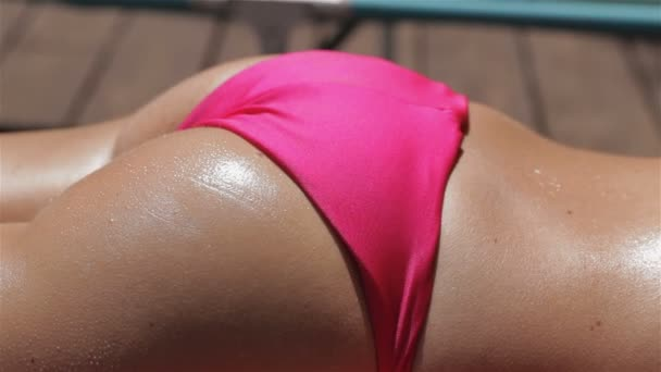 Woman lies with her back to the sun near the swimming pool