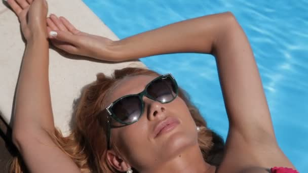 Woman relaxes on the pool edge