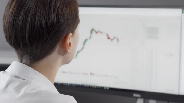 Cropped rear view shot of a woman analysing stock rates on her computer