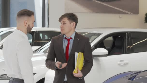 Cheerful car dealer shaking hands with a customer after giving him car keys