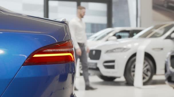 Podnikatel zkoumá auta na prodej v autosalonu