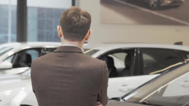 Happy mature man smiling to the camera while choosing car to buy