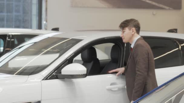 Starší muž zkoumá auta v prodeji v prodejním salonu