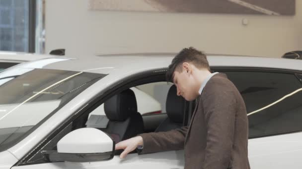 Rear view shot of a mature man looking inside a new car on sale at dealership