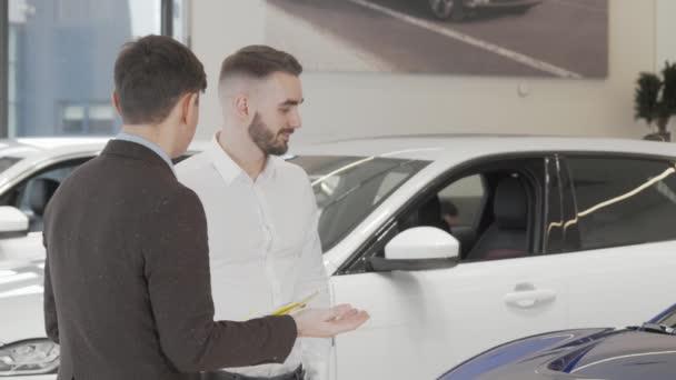 Hezký obchodník mluví s prodejcem v autosalonu