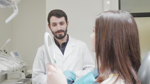Zubař mluvit s pacientem, zatímco ona se dívá do zrcadla po zubní ošetření
