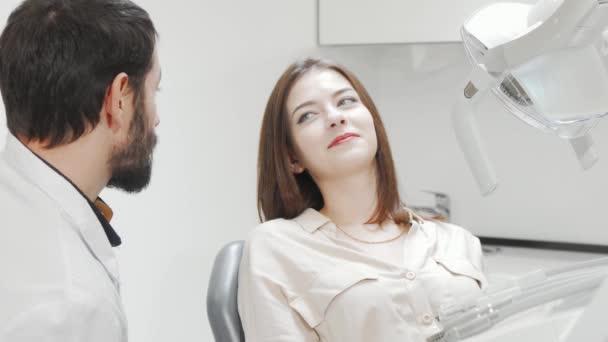 Krásná mladá žena, která má zuby zkontrolovány zubařem