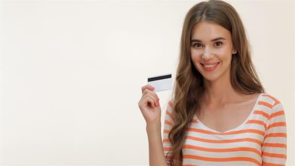attraktives Mädchen zeigt Daumen nach oben mit Kreditkarte
