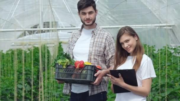 Guy pracuje na sklizeň a dívka agronom, usmíval se přímo na kameru