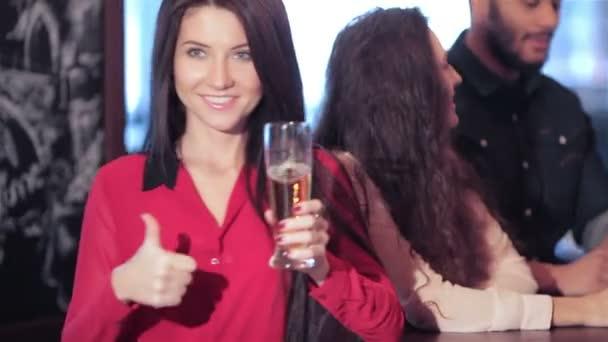 Krásná mladá dívka s pivem v společnosti přátel ukazuje palec