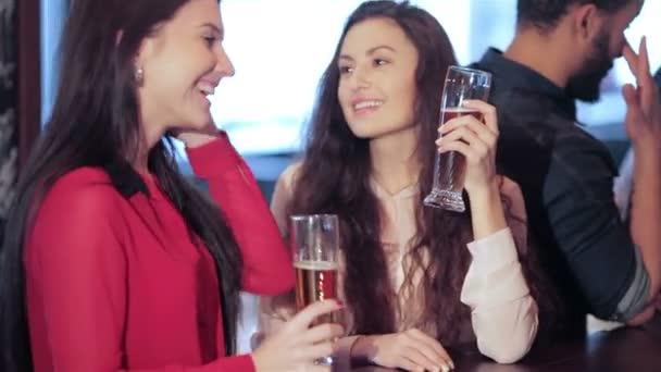 Dvě roztomilé dívky kamarádky se setkají v baru, usměvavá a vyzváněcí brýle