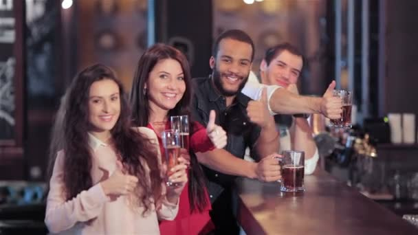 Group of girls and boys at the bar with a beer smiling and showing thumb up