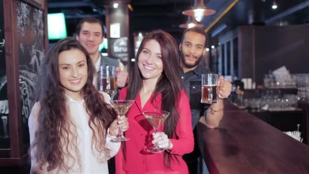 Dívky s martini a kluci se sklenicemi piva na baru pozdraví přátel
