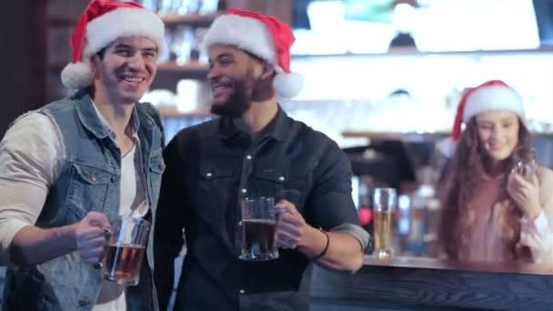 zwei Freundinnen mit Weihnachtsmützen und das Mädchen hinter der Theke mit einem Glas Bier