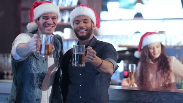 Dva přátelé v Santa klobouky a dívka za barem s pivem pozvedla sklenice