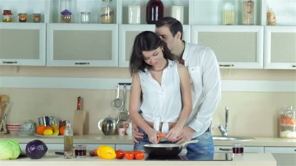 The girl chopped carrots, boy kissing a girl and add flavored oil in a frying pan