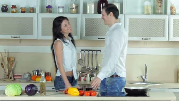 Fiatal gyönyörű pár találkozik a konyhában, csók, és ivott a szőlőlé
