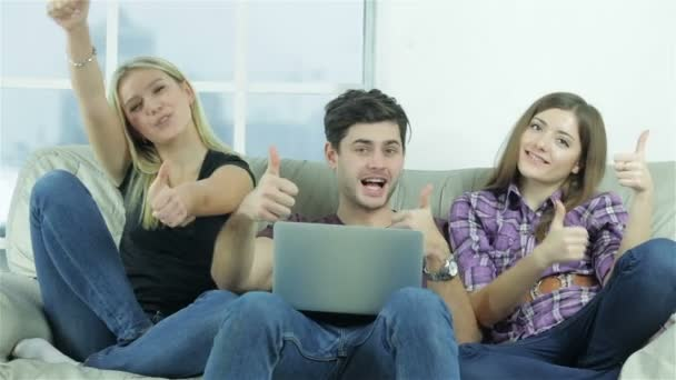 Guy and two girls show thumbs top directly into the camera