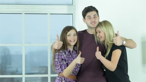 Guy and two girls show thumbs