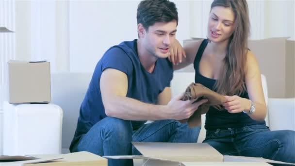 Láska pár sedí v prázdné bytě mezi boxy