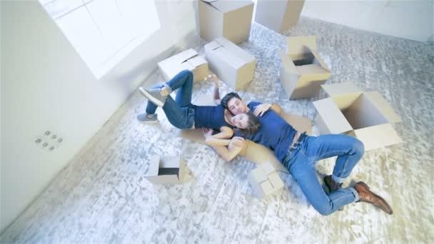 Pár, ležící na podlaze mezi boxy v prázdného bytu