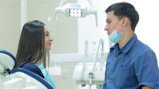 The dentist and young woman patient teeth smile directly into the camera