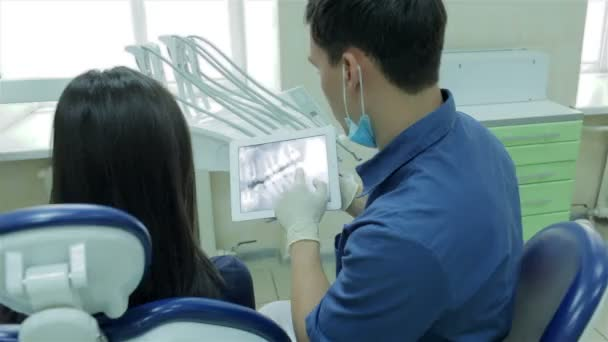 Dentist shows a patient x-ray on the tablet of her teeth and tells method of treatment channels