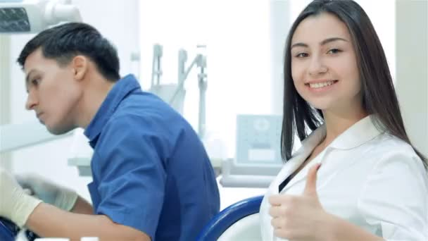Dentist is drilling the patients teeth and assistant girl smiles and thumbs up