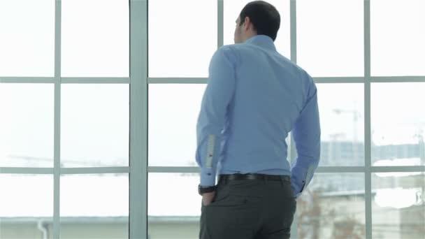 Vidám és sikeres üzletember, a hivatalos viselet órájára néz