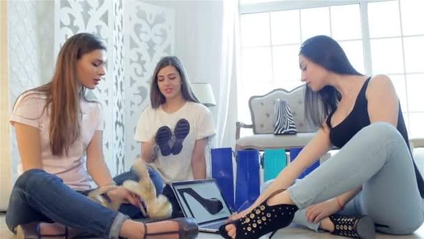 Tři přátelé sedí na podlaze se snaží na boty
