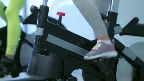 Nahaufnahme von SportBauchfüßen auf einem stationären Fahrrad im Fitnessstudio