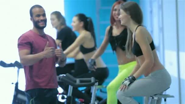 Přátelé jsou sportovci v tělocvičně a podívejte se do kamery