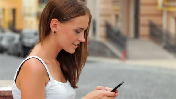Side view of a fashion woman using a smartphone sitting on a bench in the street