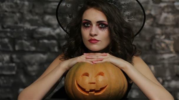 The woman-sorceress posing with pumpkin