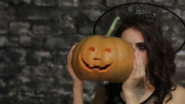 A woman-sorceress covers her face pumpkin
