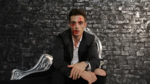 Male vampire sitting on a black sofa