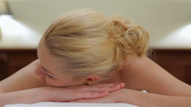 Žena při pohledu na fotoaparát a masáž
