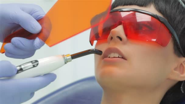 Dentist shines ultraviolet photopolymer seal on fixing it