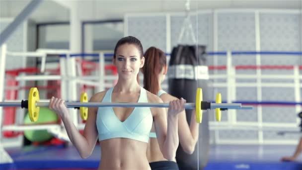 Mädchen-Athlet Übungen mit der Langhantel erfüllt ihre Fitnesstrainerin