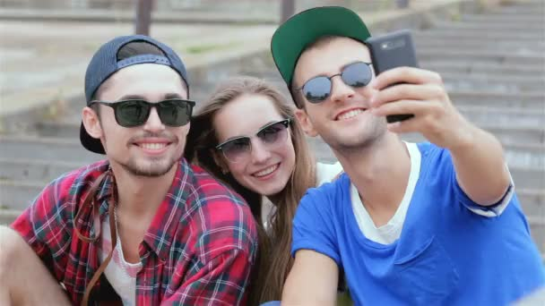 With friends sitting on the steps of making selfie