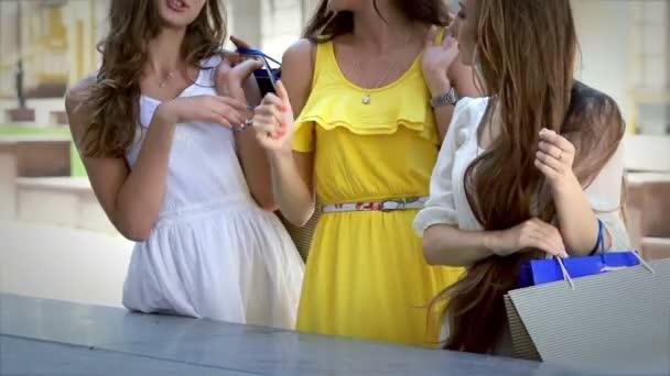 Drei Mädchen stehen vor einer Vitrine und diskutieren über ein neues Kleid