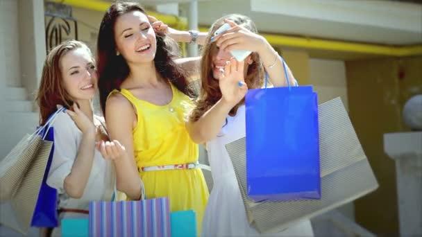 Three pretty girls-shopaholic make selfieie after shopping